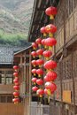 Red lanterns at traditional wooden houses in longsheng in china symbolize wealth prosperity and happiness Stock Image