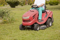 Red Lawn mower cutting grass Royalty Free Stock Image