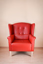 Red leather armchair against the wall on wooden floor Royalty Free Stock Images
