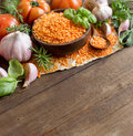 Red lentils in a bowl with tomatoes garlic and herbs on wood Royalty Free Stock Images