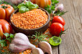 Red lentils in a bowl with tomatoes garlic and herbs on wood Royalty Free Stock Photo
