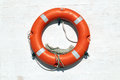 Red life buoy hanging on the wall white Stock Photos