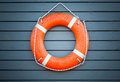 Red lifebuoy hanging on blue wooden wall of a port building Royalty Free Stock Photos