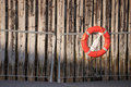 Red lifebuoy with rope on metal railings above weathered wooden wall in port Stock Photos