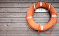 Red lifebuoy with rope on weathered wooden wall in port Royalty Free Stock Photos