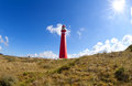 Red lighthouse tower and sun Royalty Free Stock Photo