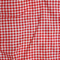 Red linen crumpled tablecloth abstract background texture of a and white checkered picnic blanket Royalty Free Stock Photography