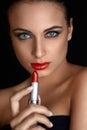 Red lips.  Beutifull Woman Doing Makeup Applying lipstick Royalty Free Stock Photo