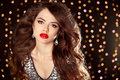 Red lips makeup, Beautiful girl with long wavy hair. fashion ear Royalty Free Stock Photo