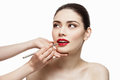 Red lipstick application professional make up artist applying bright on beautiful girl using special lip brush isolated over white Stock Photography