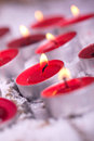 Red lit Tealights with golden flame Royalty Free Stock Image