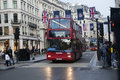 Red London buses during the rush hour in central London taking passengers to and from work and shopping crossing a box junction Royalty Free Stock Photo