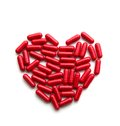 Red long pills in a heart form Royalty Free Stock Photo