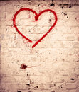 Red love heart hand drawn on brick wall grunge textured background trendy street style Stock Image