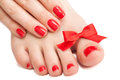 Red manicure and pedicure with a bow. isolated Royalty Free Stock Photos