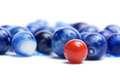 Red marble with blue marbles a standing out in a crowd of on a white background Stock Photography