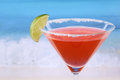 Red Martini cocktail with a lime on the beach Royalty Free Stock Photo