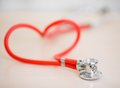 Red medical stethoscope in shape of heart on table Royalty Free Stock Photo