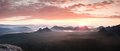 Red misty  landscape panorama in mountains. Fantastic dreamy sunrise on rocky mountains.  Foggy misty valley below Royalty Free Stock Photo