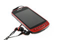 Red mobile phone with headsets Royalty Free Stock Photo