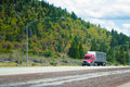 Red modern semi truck with low cab and soft tent trailer move on Royalty Free Stock Photo