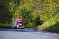 Red modern semi truck with trailer going up hill in autumn trees Royalty Free Stock Photo