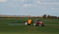 Red modern tractor pulling a crop sprayer Royalty Free Stock Photo