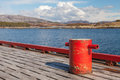 Red mooring bollard on wooden pier with seascape a background Royalty Free Stock Images