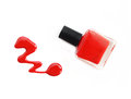 Red nail polish bottle with splatters  on white background. Royalty Free Stock Photo
