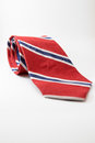 Red neck tie with blue and white stripes layed on white background.