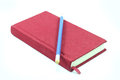 Red notebook and blue pencil Royalty Free Stock Photo