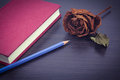 Red notebook and dry rose on black wooden background in vintage Royalty Free Stock Photo