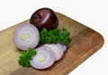 Red onions on wooden chopping board Stock Photography