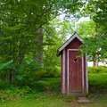 Red outhouse in the countryside of Unguri in Lithuania Royalty Free Stock Photo