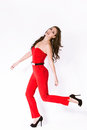 Red overalls fashion girl in elegant and high heel shoes in motion full body shot Royalty Free Stock Image