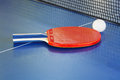 Red paddle, tennis ball on blue ping pong table Royalty Free Stock Photo