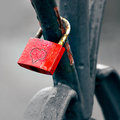 Red padlock with heart locked to bridge railing on rainy gloomy day Stock Photos