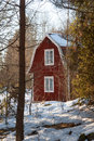 Red painted Swedish wooden house in a wintry landscape Royalty Free Stock Photography