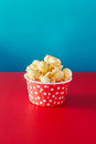 Red paper cup with popcorn against vibrant background. Royalty Free Stock Photo