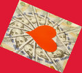 Red paper heart and hundred dollar bills