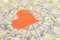 Red paper heart and hundred dollar bills background