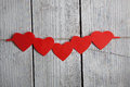 A red paper hearts hanging on the clothesline in front of wooden background Royalty Free Stock Photo