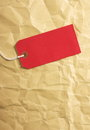 Red paper luggage tag a blank or gift on a crumpled brown wrapping background with room for your text Stock Photography
