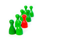 Red pawn in a line up of green pawns against white background Stock Photography
