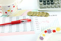 The red pen cup calculator and money coins on business graph closeup picture Stock Photo