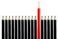 Red pencil among black pencils Stock Photo