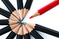 Red pencil standing out from the circle of black pencils Royalty Free Stock Photo