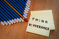Red pencil standing out from crowd of blue pencils and post it o differrent thinking word on wooden table business success Royalty Free Stock Images