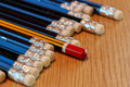 Red pencil standing out from crowd of blue pencils on wooden tab Royalty Free Stock Photo