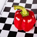 Red Pepper With A Ponytail On A Chessboard.